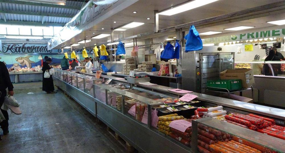 Un marchand dans la halle du marché des Merisiers